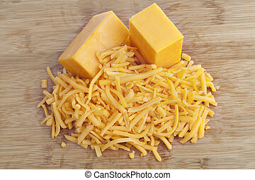 Shredded cheddar cheese on a brown background
