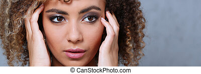 A beautiful black woman portrait. Tests the emotion of bewilderment of fear of terror confusion beauty fashion style mulatto curly hair with white locks eye view of the camera