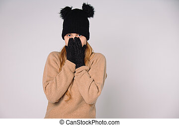 A blue-eyed girl in black winter hat and gloves holds her hands to her face. Grey background with space.
