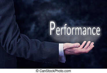A businessmans hand holding the word, Performance.