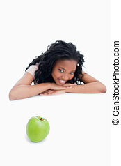 A green apple with a smiling girl in the background