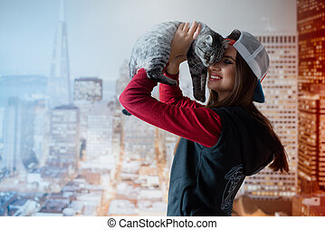 A smiling girl holds a cat by the face