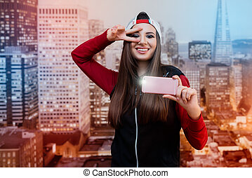 A smiling girl with black eyes. Dressed in black with a red sweater and a cap turned backwards. Itself photographed on a pink smartphone. In the background images of the city at the wallpaper.