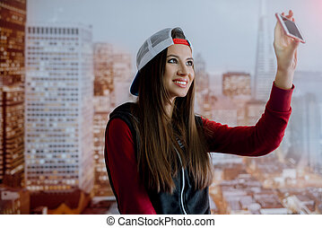 A young and positive girl is photographed on her smartphone in her room on the background of the city depicted on the wallpaper.