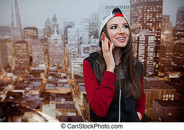 A young and positive girl is talking on the phone in her room against the backdrop of the city depicted on the wallpaper.
