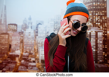 A young and positive girl with sunglasses is talking on the phone in her room against the background of the city depicted on the wallpaper.