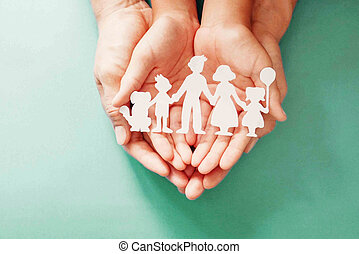 Adult and children hands holding paper family.