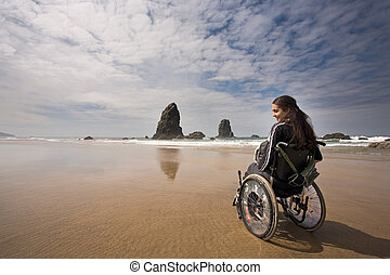 Beautiful young woman in a wheel chair visiting Canon Beach in Oregon, USA.