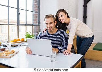 Affectionate happy couple using a laptop computer on their kitchen counter spread with frosh rolls and fruit as they sit and stand arm in arm