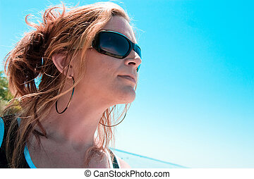 A woman looks at the clear blue sky
