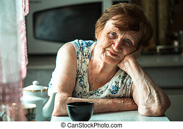 An elderly pensioner sits at a table in her home. Portrait.