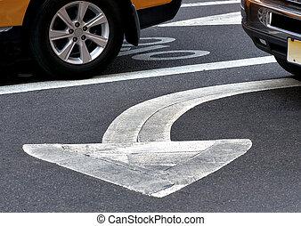 Arrow sign on asphalt