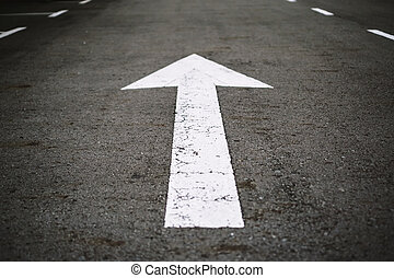 Arrow Sign on Asphalt Road