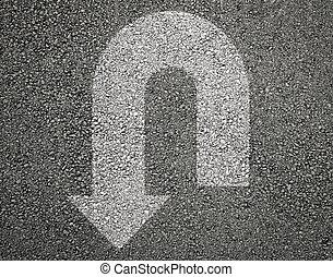 Arrow u turn sign on asphalt