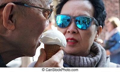 Asian senior couple enjoying ice cream during vacation holiday trip