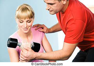 Image of pretty girl exercising with barbell in hand while the trainer assisting her