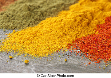 Close-up of assorted loose powder spices on wood.