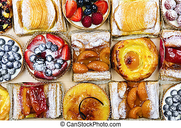 Background of assorted fresh sweet tarts and pastries from above