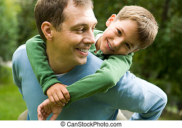 Image of happy man holding his son while having fun