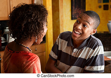 Attractive African-American woman and teen laugh in kitchen