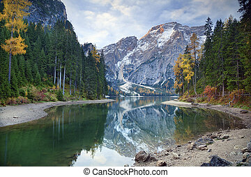 Idyllic lake surrounded by colourful forest in the Italian Alps during autumn morning.
