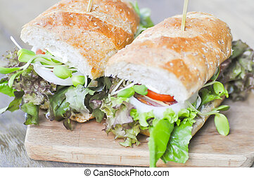 baguette sandwich with ham, tomato, and lettuce