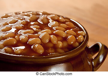 Baked beans in tomato sauce, in a brown pot.