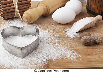 Baking ingredients and tools on brown wood cutting board