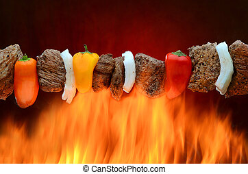Skewered meat and vegetable kabob over hot barbecue flame.