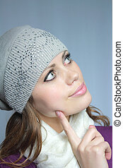 blue-eyed brown-haired woman in a winter cap