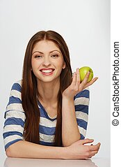 Beautiful brunette woman with a green apple