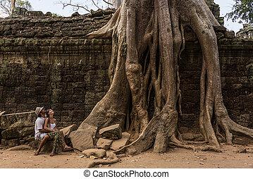 Beautiful Couple looking at Giant Roots at Angkor Wat Cambodia.