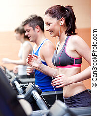 Beautiful female athlete standing on a running machine listening to the music in a fitness centre