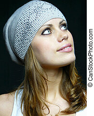beautiful girl in a grey cap with pastes