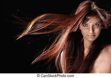 Attractive girl with red hair on a black background