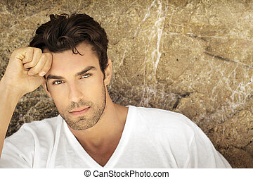 Portait of young man outdoors with very handsome face in white casual shirt against natural background