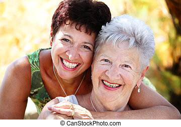 close-up portrait of a beautiful senior mother and daughter smiling at the camera
