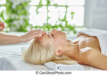 Beautiful woman with closed eyes getting a massage in the spa s