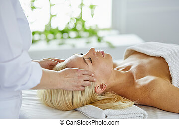 Beautiful woman with closed eyes getting a massage in the spa salon