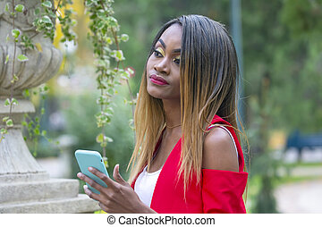 Beautiful young African girl with phone in her hands