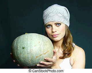 beautiful young blue-eyed girl with a pumpkin in hands