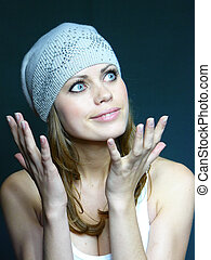 young brown-haired woman in a grey cap with pastes