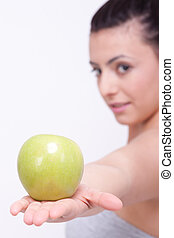 beautiful young brunette girl with a green apple