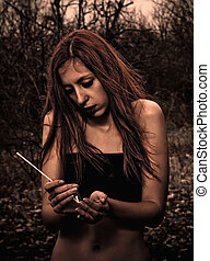 Beautiful young sad girl with match in hands