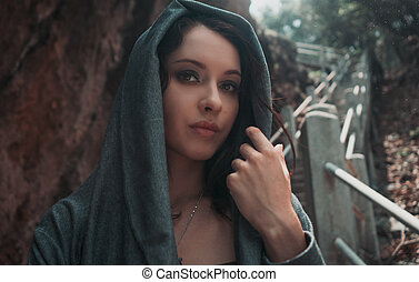 Beautiful young sexy girl with bright make-up in a grey hood