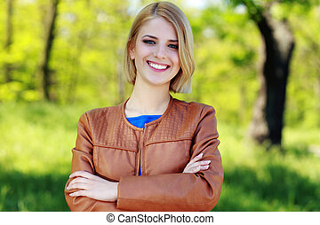 beautiful young smiling girl standing with hands folded in park