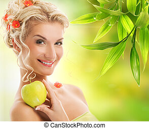 Beautiful young woman with ripe green apple