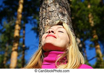 beauty woman breathes near trunk of pine