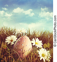 Big easter egg in the grass with daisies