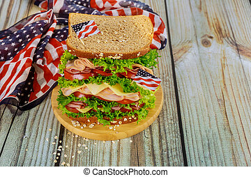 Big sandwiche with ham, cheese and tomato for american holiday table.